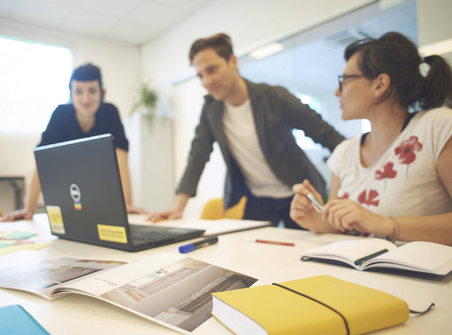 Foto emozionale per la voce Aziende, con un uomo in piedi, una donna in piedi ed una seduta attorno ad un PC | Fabbrica delle Idee | Coworking | Maniago