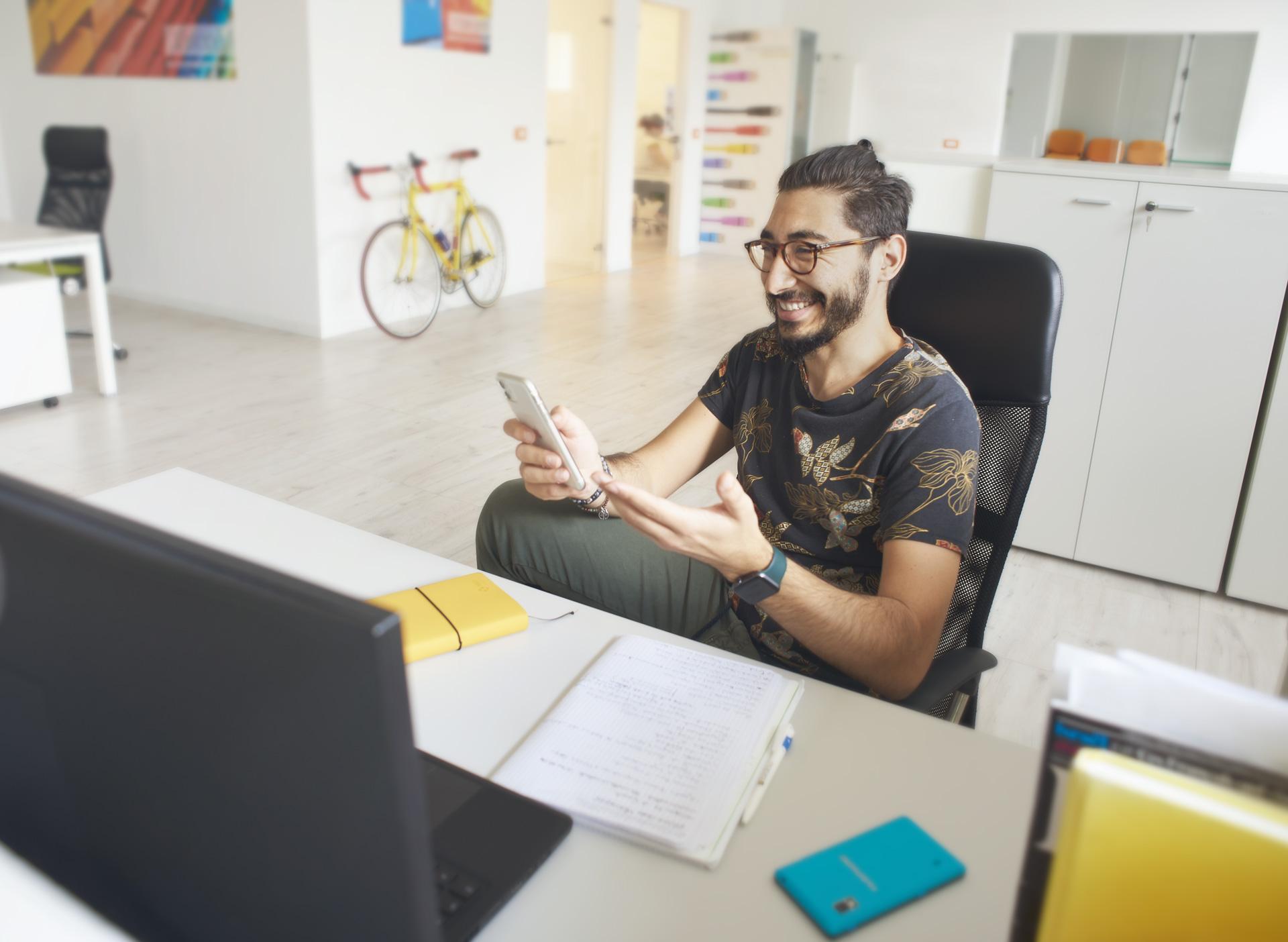 Foto emozionale per la voce Freelance, con ragazzo sorridente con barba e occhiali seduto alla scrivania Freelance | Fabbrica delle Idee | Coworking | Maniago