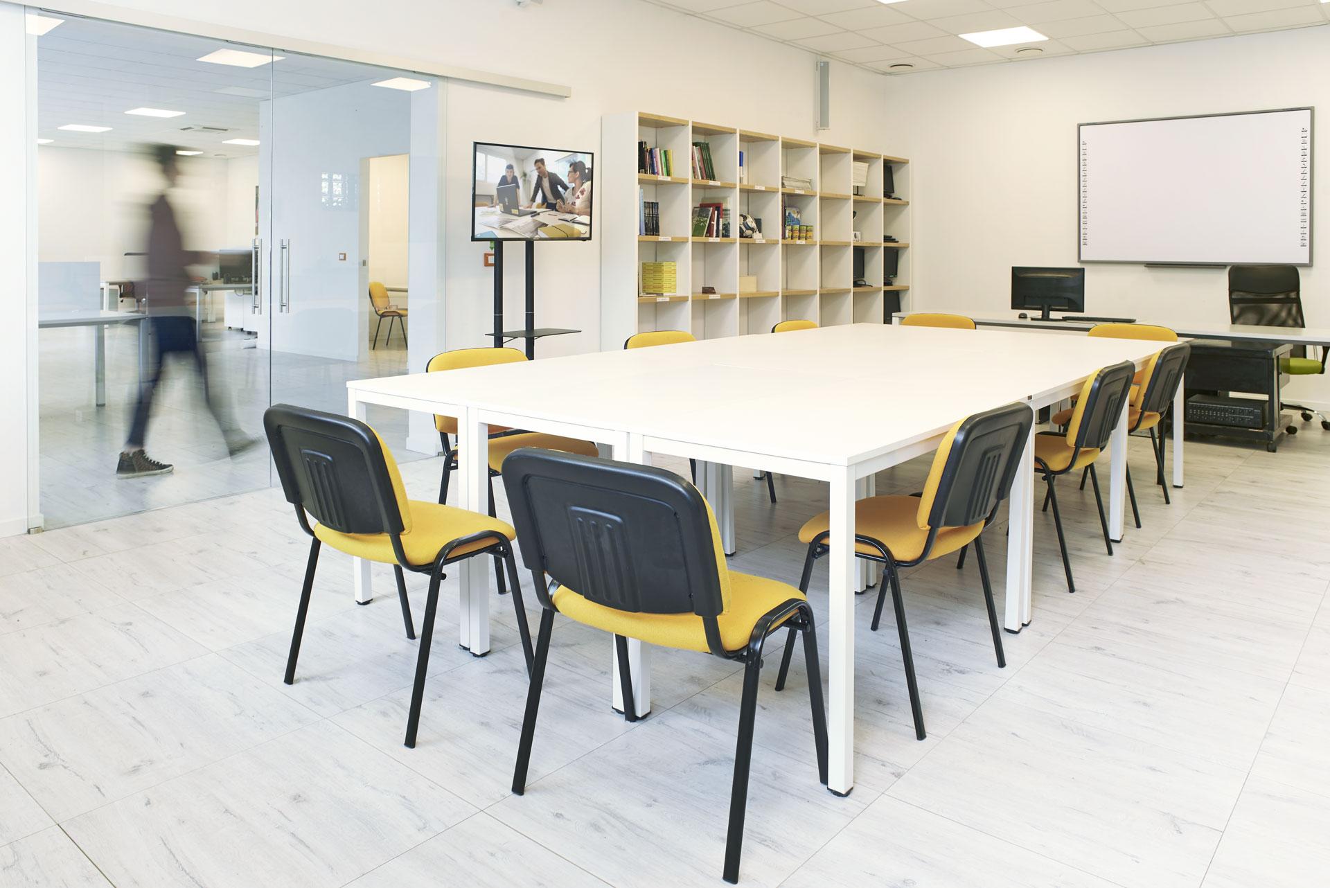 Sala Riunioni allestita per incontro con tavolo centrale, sedie e televisore