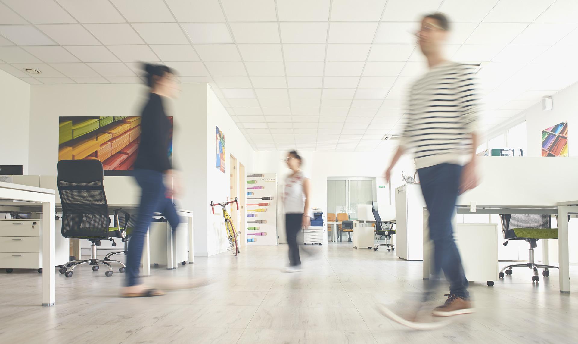 Foto Homepage Fabbrica delle Idee | Coworking | Maniago Tre persone che camminano all'interno della FDI