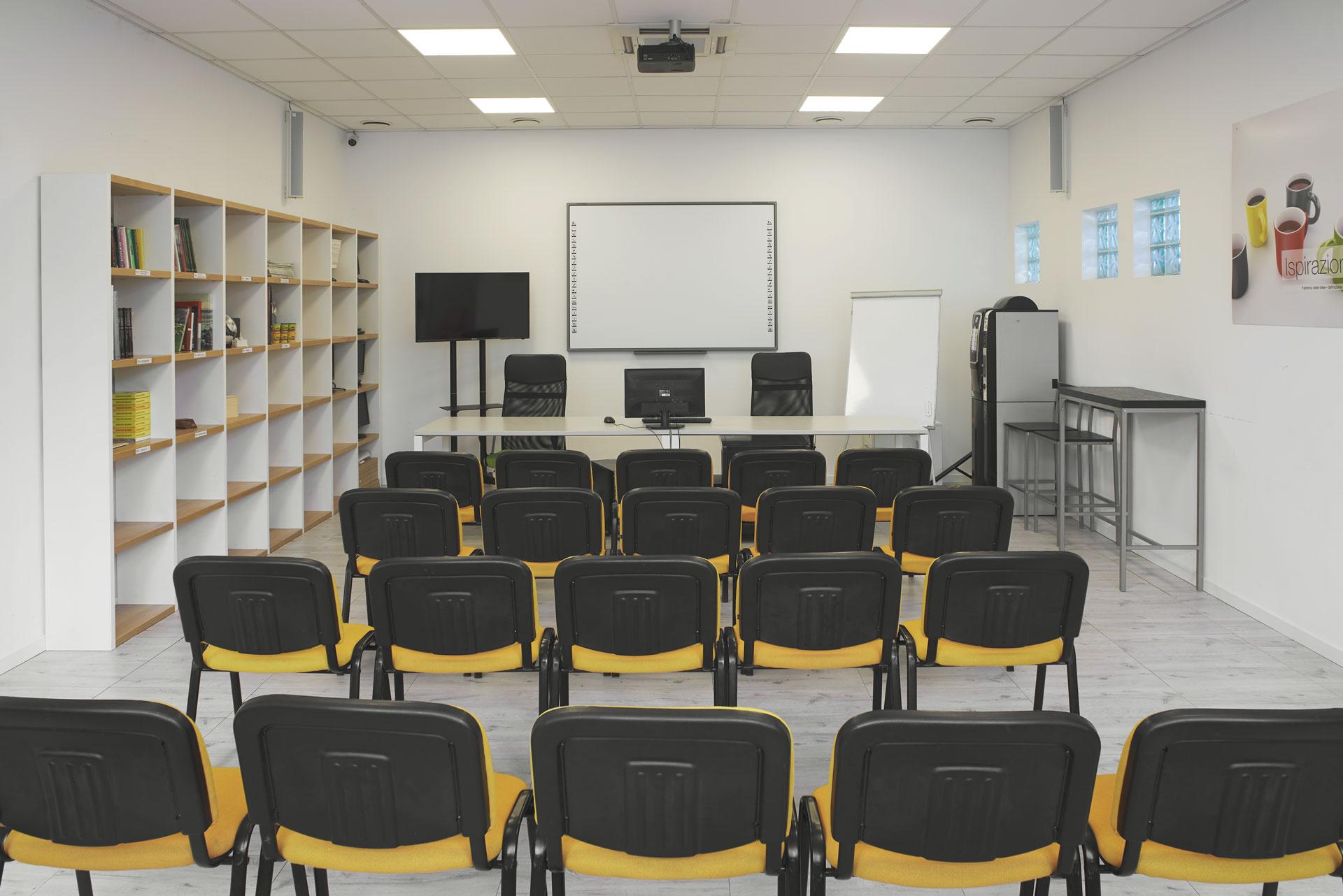Sala Riunioni allestita per una conferenza con sedie allineate che guardano la lavagna ed il televisore